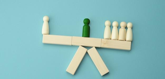 Figures en bois d'hommes sur une balançoire, entre eux un négociateur
