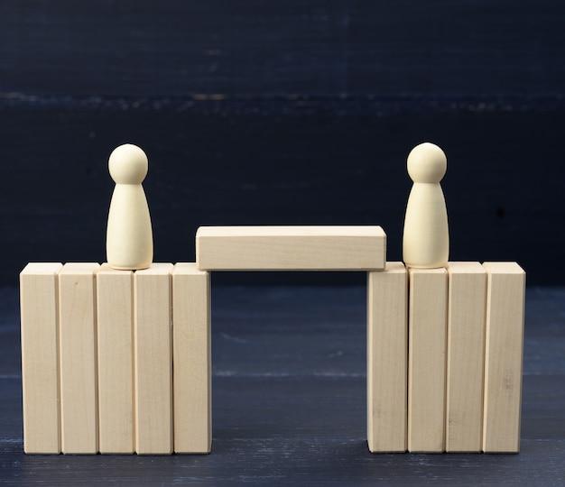Figures en bois d'hommes sur un pont fait de blocs