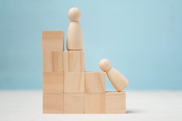 Figures en bois de personnes sur une échelle de carrière. l'un d'eux abandonne.