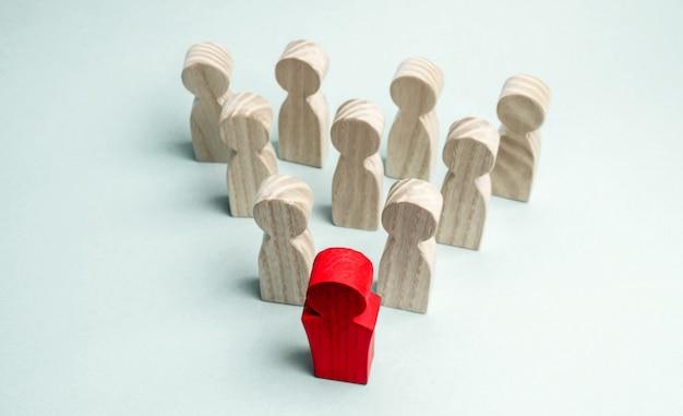 Figures en bois de personnes. le patron de l'équipe commerciale indique la direction du mouvement