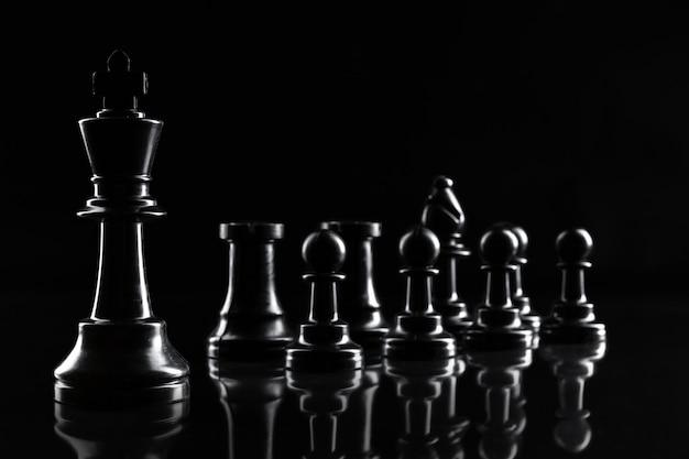 Figures d'échecs sur fond noir foncé se bouchent