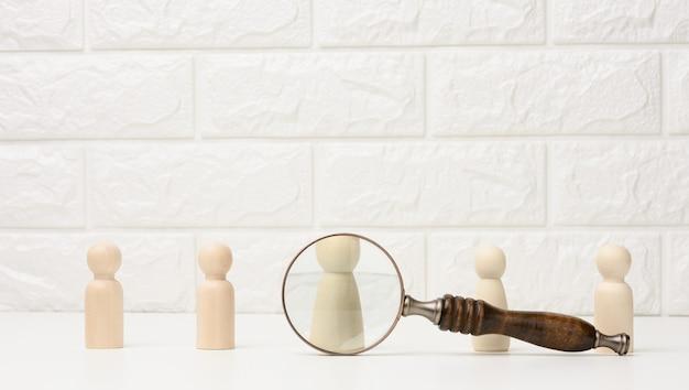Des figures d'hommes en bois se tiennent sur un fond blanc et une loupe. concept de recrutement, recherche d'employés talentueux et capables, évolution de carrière
