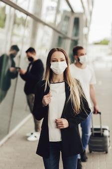 Des figures de jeunes dans des masques de protection près de l'aéroport. voyager en toute sécurité pendant une pandémie. concept de voyage en avion, de quarantaine et de pandémie