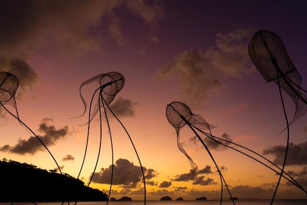 Figures de méduses sur un mur de coucher de soleil coloré.