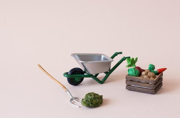 Figures réalistes d'outils de ferme ou de jardin avec boîte de légumes