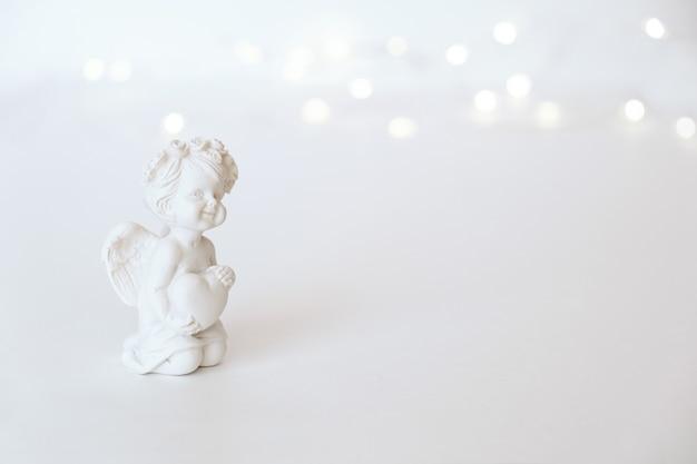 Figurine d'un ange cupidon avec un arc sur fond rose. la saint-valentin.