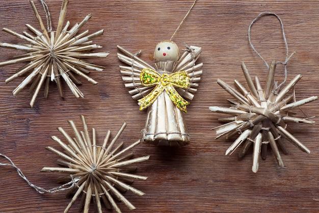 Figurine ange jouet vintage sur table en bois patiné avec des flocons de paille