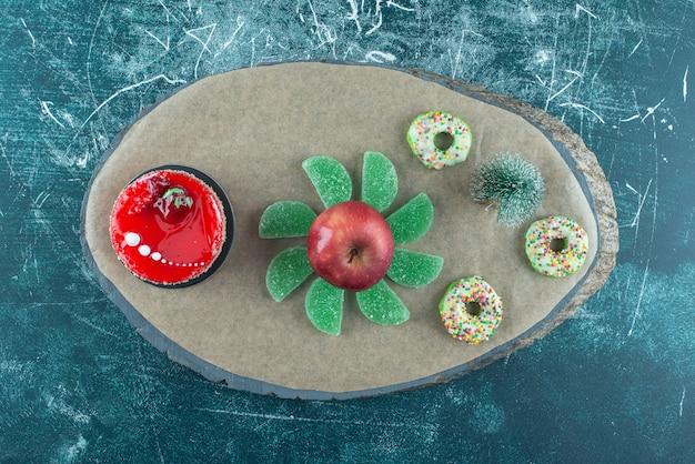Figurine d'arbre, gâteau, marmelades, beignets et une pomme sur une planche sur bleu.