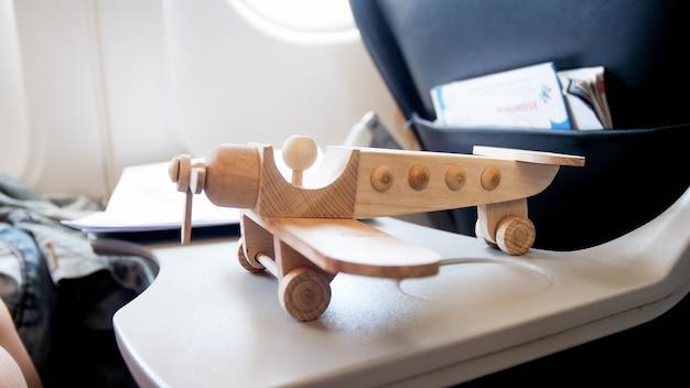 Figurine d'avion en bois jouet sur table dans un avion à réaction moderne.