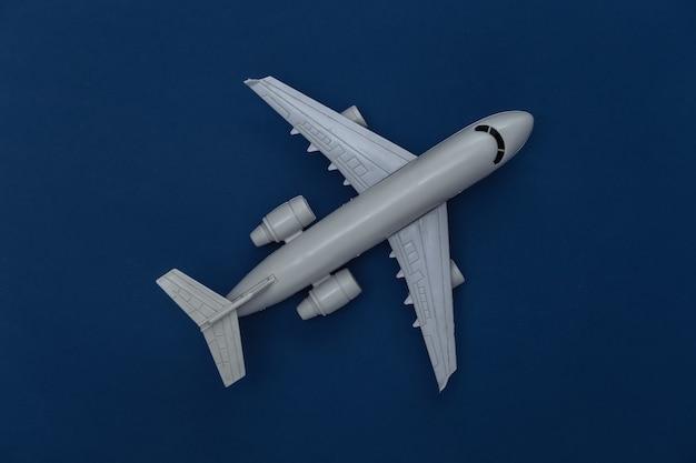 Figurine d'avion de passagers sur fond bleu classique. couleur 2020. vue de dessus.