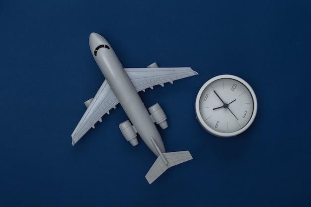 Figurine d'avion de passagers et horloge sur fond bleu classique. couleur 2020. vue de dessus.