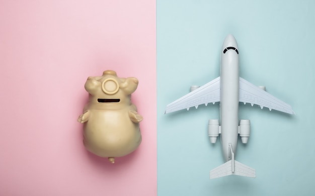 Figurine avion, tirelire sur pastel rose-bleu.