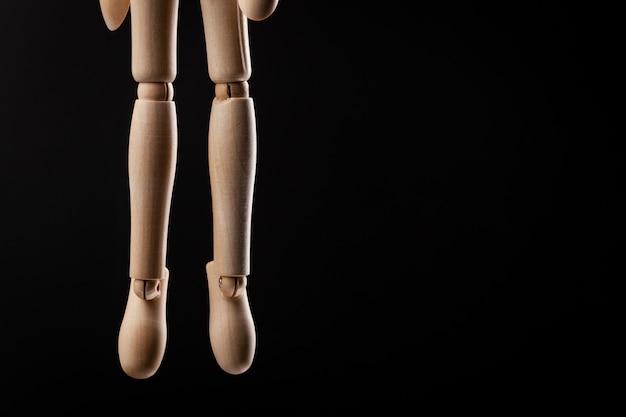 Figurine en bois pendue à une corde isolée sur fond noir