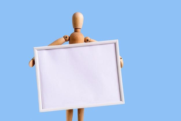 Figurine en bois tenant un cadre pour votre texte