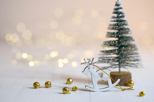 Figurine de cerf, sapin de noël et boules d'or sur la table