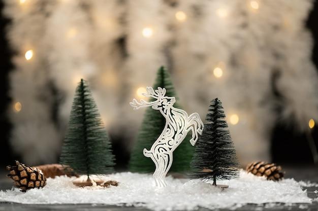 Une figurine de cerf et sapins verts sur fond de vacances neige artificielle