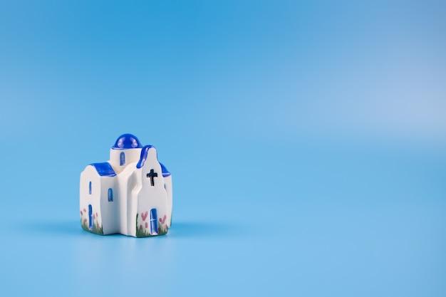 Figurine d'une chapelle grecque, sur fond bleu. carte postale, concept de voyage.