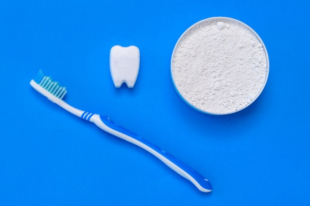 La figurine de dent sourit à côté de la poudre à dents et de la brosse à dents. mise à plat.