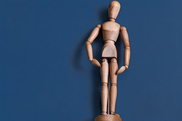 La figurine d'homme en bois sur bleu.