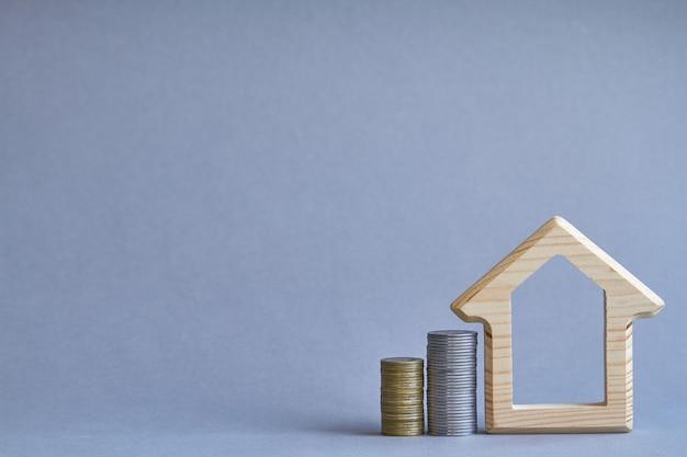 Figurine de maison en bois avec deux colonnes de pièces de monnaie voisines sur fond gris