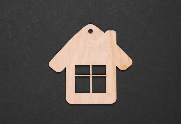Figurine de maison en bois ou porte-clés sur fond noir. vue de dessus