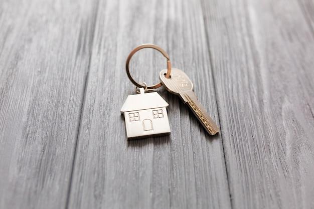 Figurine de maison et clé sur table