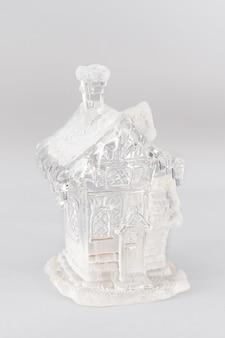 Figurine de noël en verre d'une maison avec de la neige. composition de noël sur fond gris. concept de noël à la maison doux à la maison