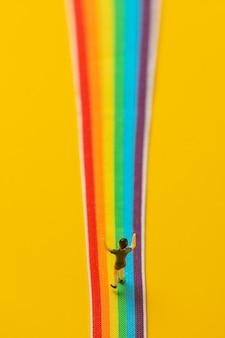 Figurine de petit garçon debout sur une bande lgbt arc-en-ciel