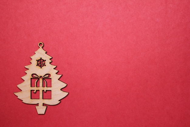 Figurine sapin de noël en bois avec un cadeau sur fond rouge. espace de copie.