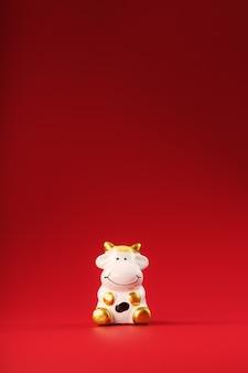 Figurine d'une vache sur fond rouge, espace libre pour le texte