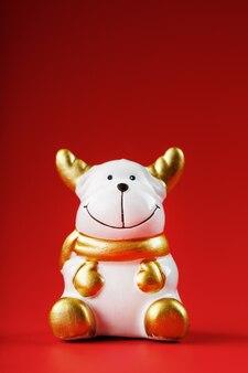 Figurine de vache de noël sur un mur rouge. symbole de la nouvelle année du taureau 2021. isoler
