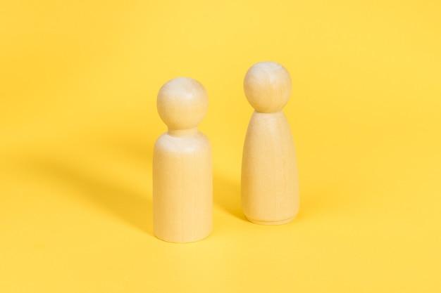 Figurines en bois de l'homme et de la femme sur fond jaune
