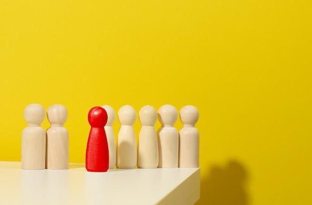 Figurines en bois d'hommes et une rouge sur fond bleu. concept de leader et de recrutement. personnalité toxique dans l'équipe