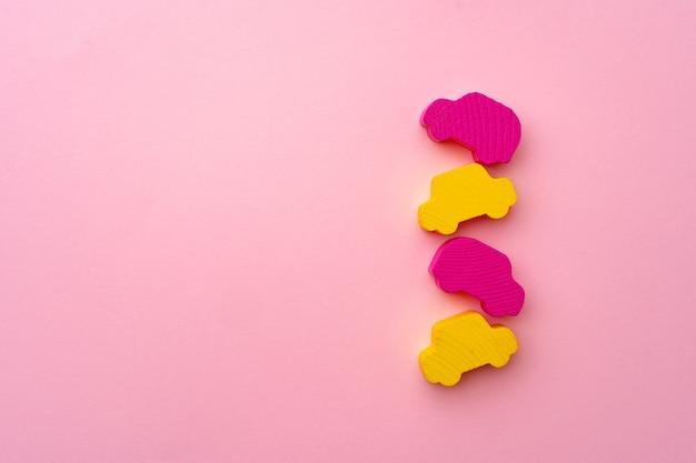 Figurines en bois de petites voitures sur la surface du papier rose