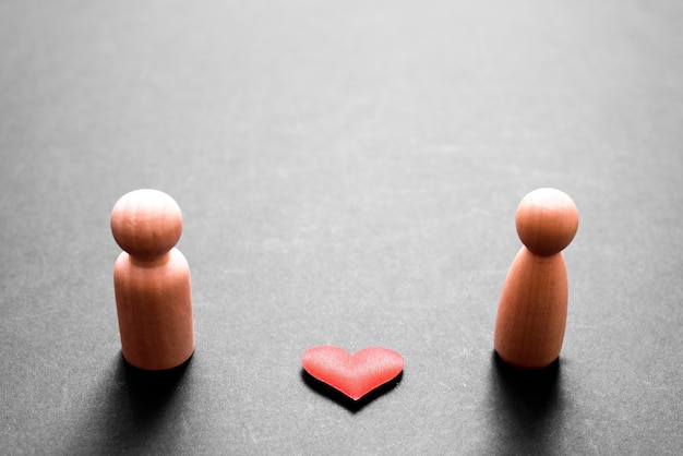 Figurines en bois représentant un couple d'homme et de femme amoureux, avec un beau coeur rouge, isolé sur fond noir.