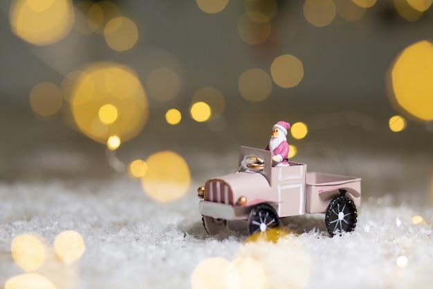 Figurines décoratives d'un thème de noël. la statuette du père noël monte sur une voiture miniature avec une remorque pour cadeaux.