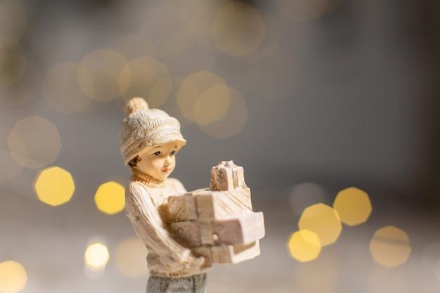 Figurines décoratives sur le thème de noël, statuette d'une jeune fille tenant des boîtes avec des cadeaux pour noël dans ses mains,