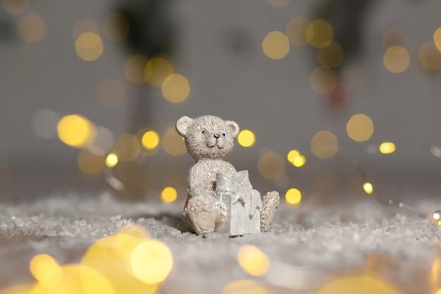 Figurines décoratives d'un thème de noël. statuette d'un ours en peluche avec une écharpe, asseyez-vous à côté de la boîte avec un cadeau de noël.