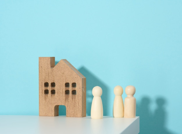 Figurines familiales en bois, maison modèle sur fond bleu. achat immobilier, concept de location. déménagement dans de nouveaux appartements