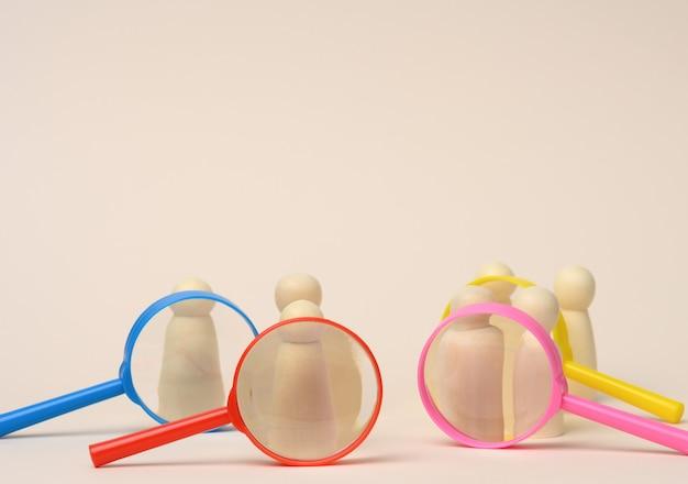 Des figurines d'hommes en bois se tiennent sur un fond beige et une loupe en plastique. concept de recrutement, recherche d'employés talentueux et capables, évolution de carrière