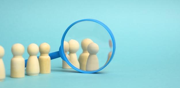 Des figurines d'hommes en bois se tiennent sur un fond bleu et une loupe en plastique. concept de recrutement, recherche d'employés talentueux et compétents, évolution de carrière, espace de copie