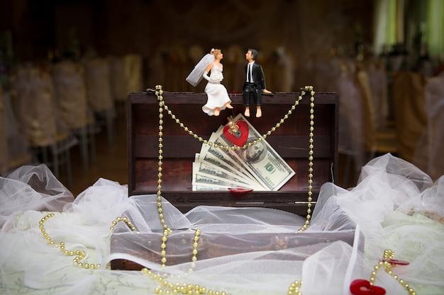 Figurines des mariés assis sur une boîte
