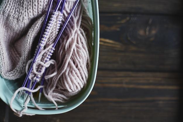 Fil en bobines et aiguilles à tricoter sur table en bois. loisirs à la maison. chaussette tricotée à la main avec aiguilles et pelote de laine