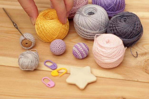 Fil coloré, doigts et crochet sur fond en bois.