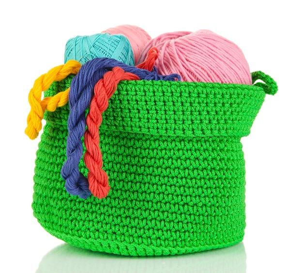 Fil coloré pour tricoter dans le panier vert isolé sur blanc