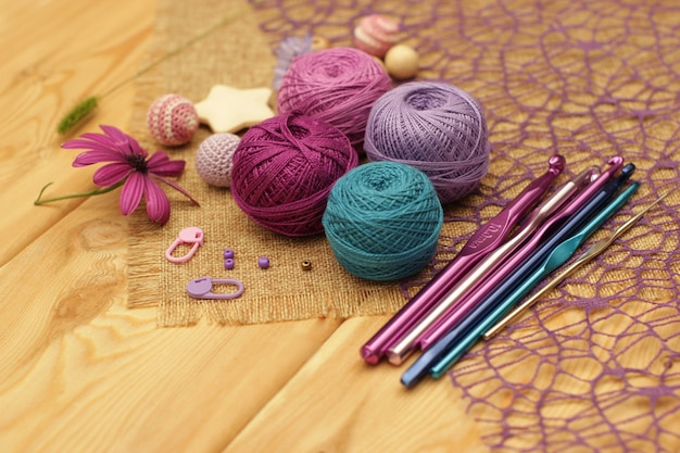 Fil coloré pour tricoter sur une table en bois marron.