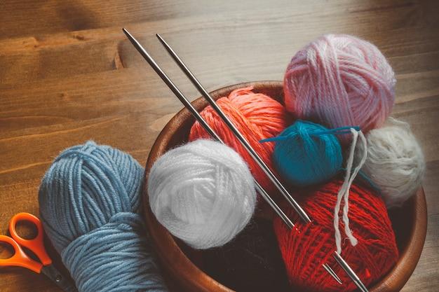 Fil de couleur pour tricoter avec des rayons, une aiguille en plastique et des ciseaux
