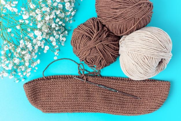 Fil et un crochet à tricoter sur fond bleu