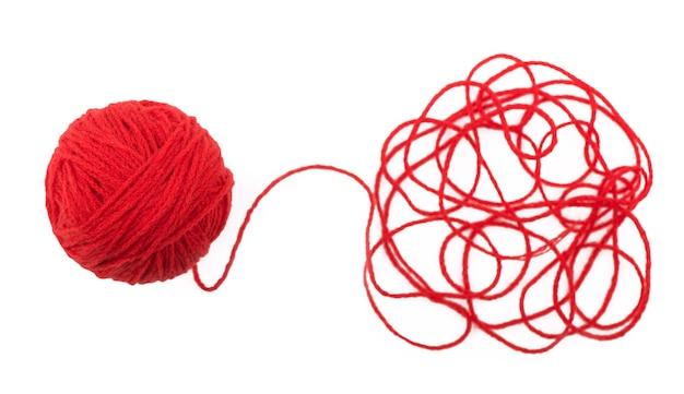 Fil emmêlé et boule de laine rouge sur une surface blanche