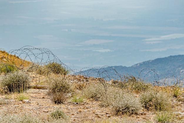 Fil de fer barbelé sur la colline du mont hermon avec vue sur les champs